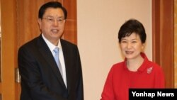 박근혜 한국 대통령이 11일 청와대를 방문한 장더장 중국 전국인민대표회의 상무위원장(왼쪽)과 인사하고 있다.
