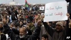 ຜູ້ປະທ້ວງຊາວລີເບຍຄົນນຶ່ງ ຊູປ້າຍຄຳຂວັນ ຮຽກຮ້ອງໃຫ້ທ່ານ Moammar Ghadafi ຜູ້ນຳຂອງລີເບຍ ລາອອກ ໃນລະຫວ່າງ ການໂຮມຊຸມນຸມປະທ້ວງຕໍ່ຕ້ານລັດຖະບານ ທີ່ເມືອງ Benghazi (25 ກຸມພາ 2011)