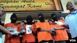 Empat orang berbaju tahanan warna oranye dikawal sejumlah petugas polisi bersenjata lengkap di Polresta Solo, Rabu siang, 1 Juni 2016 (Foto: VOA/Yudha).