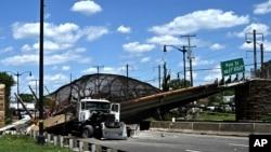 اے پی کی تصویر میں حادثے کے بعد پیدل چلنے والوں کے پل کے نیجے دبا ٹرک دیکھا جا سکتا ہے