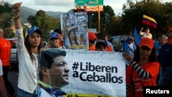 "FILE - Patricia de Ceballos, left, wife of jailed former Mayor Daniel Ceballos, stands next to a banner reading ""Release Ceballos"" while campaigning to become mayor herself in San Cristobal, Venezuela, May 23, 2014."