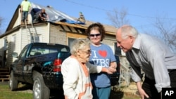 Illinois Governor Pat Quinn (r) speaks with Edith Raynes, 86, in front of her damaged home in Harrisburg, Ill., Feb. 29, 2012.