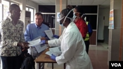 Staff hand out health forms to arriving passengers, Lungi international airport, Sierra Leone, Feb. 3, 2015. (Nina deVries/ VOA)