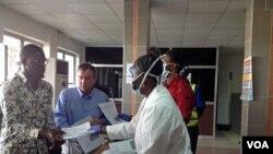 2015年2月3日塞拉利昂隆吉国际机场: 工作人员向来访旅客发伸手健康表格