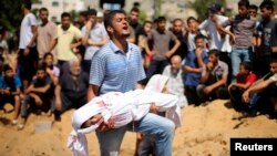 A Palestinian man carries the body of a girl from the Abu Nejim family, whom medics said was killed along with other eight family members by an Israeli air strike in the northern Gaza Strip, August 4, 2014.