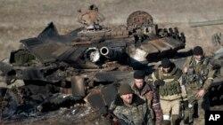 Сепаратисти оглядають знищений українських танк.
