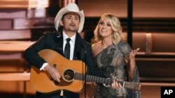 FILE - Hosts Brad Paisley, left, and Carrie Underwood speak at the 50th annual CMA Awards at the Bridgestone Arena in in Nashville, Tennessee, Nov. 2, 2016.