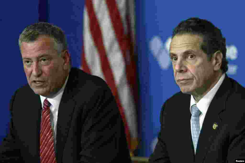 New York City Mayor Bill de Blasio (left) and New York Gov. Andrew Cuomo discuss the city's first confirmed Ebola case at a news conference at Bellevue Hospital, New York City, Oct. 23, 2014.