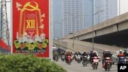 Các phương tiện giao thông đi ngang qua một tấm bảng có nội dung về Đại hội Đảng Cộng sản Việt Nam lần thứ 12, ngày 19 tháng 1 năm 2016.