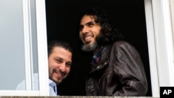 FILE - In this June 5, 2015 file photo, Abu Wa'el Dhiab, from Syria (r) and Adel bin Muhammad El Ouerghi, of Tunisia, both freed Guantanamo Bay detainees, look out the window of their shared home in Montevideo, Uruguay. Abu Wa'el Dhiab, who disappeared in June 2016 in Uruguay, setting off alarm bells in neighboring countries and recriminations in Washington, has reappeared in Venezuela according to Uruguay's Foreign Minister Rodolfo Nin Novoa on Wednesday, July 27, 2016.