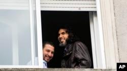 Abu Wa'el Dhiab, de Siria (der.) y Adel bin Muhammad El Ouerghi, de Túnez, exdetenidos de Guantánamo en la ventana del apartamento que compartían en Uruguay, antes de que Dhaib huyera del país y reapareciera en Venezuela.