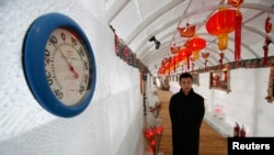 A waiter stands next to a thermometer indicating -10 degree reading during a photo opportunity at the Ice Palace in Shangri-La Hotel in the northern city of Harbin, Heilongjiang province January 6, 2014. The Ice Palace, which is built by ice bricks, is op
