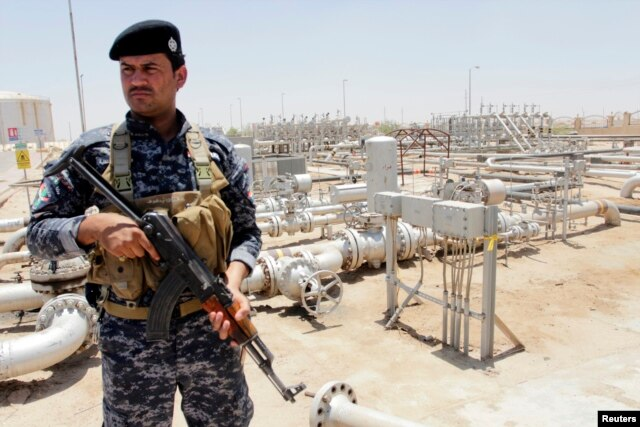 A member from the oil police force stands guard at Zubair oilfield in Basra, southeast of Baghdad, June 18, 2014.