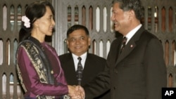 Burma's opposition leader Aung San Suu Kyi, left, shakes hands with Thai Deputy Prime Minister Chalerm Yubumrung during their meeting at Government House in Bangkok, Thailand, May 31, 2012.