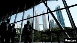 2019年6月24日在馬來西亞參加亞洲石油天然氣會議的人們走過吉隆坡雙子塔為背景的走廊。
