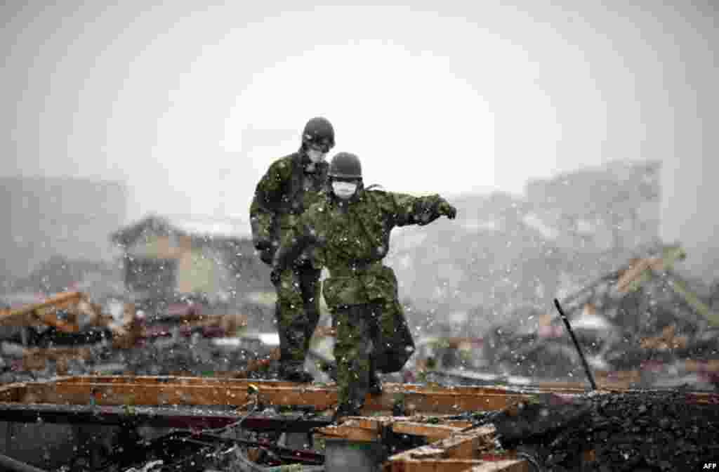 Members of the Japan Self-Defense Force make their way through the ruins of the devastated residential area in Otsuchi as heavy snow falls March 16, 2011. In the fishermen town of Otsuchi in Iwate prefecture, 12,000 out of a population of 15,000 have disa