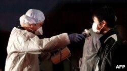 Человека, эвакуированного из района аварийной АЭС в префектуре Фукусима, проверяют на наличие радиоактивного загрязнения. 13 марта 2011 года