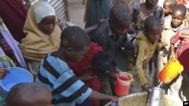 Children from southern Somalia get cooked food at a local NGO's compound in Mogadishu, Somalia, Sept.14, 2011.