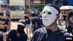 Para demonstran Hong Kong mengenakan topeng dan penutup wajah lainnya dalam aksi protes hari Jumat (4/10).