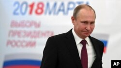Russian President Vladimir Putin arrives to vote at a polling station during Russia's presidential election in Moscow, Russia, March 18, 2018.