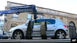 Car is towed away after its driver tried to ram through a gate of the presidential Elysee Palace, visible in background, Paris, Dec. 26, 2013.