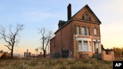 FILE - A photo shows a graffiti-marked abandoned home north of downtown Detroit, in the background, Oct. 24, 2013.
