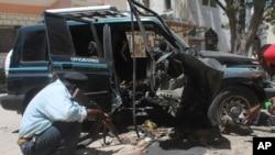Polisi Somalia memeriksa rongsokan mobil setelah ledakan di Mogadishu hari Senin (21/4).