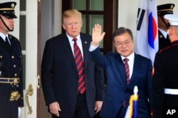 FILE - South Korean President Moon Jae-in waves as he is welcomed by U.S. President Donald Trump to the White House in Washington, May 22, 2018.