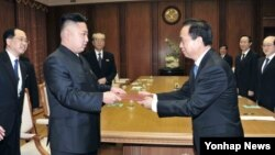 지난해 11월 중국 공산당 대표단으로부터 시진핑 공산당 총서기의 친서를 전달받은 김정은 북한 국방위원회 제1위원장(왼쪽). (자료사진)