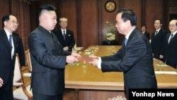 지난달 30일 방북 중인 중국 공산당 대표단으로부터 시진핑 공산당 총서기의 친서를 전달받은 김정은 북한 국방위원회 제1위원장(왼쪽). (자료사진)