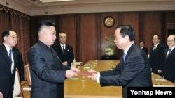 30일 방북 중인 중국 공산당 대표단으로부터 시진핑 공산당 총서기의 친서를 전달받은 김정은 북한 국방위원회 제1위원장(왼쪽).