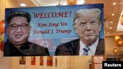 A welcoming banner with images of U.S. President Donald Trump and North Korean leader Kim Jong Un hangs at a South Korean restaurant ahead of USA-DPRK summit in Hanoi, Vietnam February 22, 2019.
