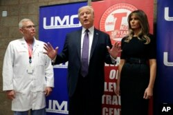 President Donald Trump talks as first lady Melania Trump and surgeon Dr. John Fildes listens at the University Medical Center after Trump met with survivors of the mass shooting, Oct. 4, 2017, in Las Vegas.