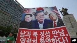Yon pannkat ki apiye somè amerikano-nò-koreyen an, montre Prezidan Trump (USA - adwat), Prezidan Moon Jae-in (Kore di Sid, nan mitan) ak lidè Kore di Nò a (Kim Jong Un, a goch). (Sewoul, Kore di Sid, 27 avril 2018).