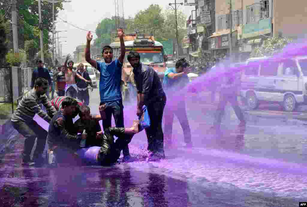 Kashmiri government employees demonstrate as riot police spray purple-dyed water during a protest march in Srinagar. Indian police detained dozens of government employees as they tried to stage a protest march demanding the regularisation of contractual jobs and an increase in salary.