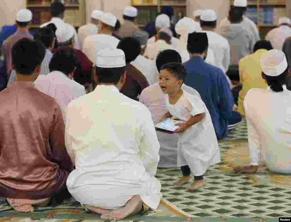 A child shouts at his father during tarawih prayers before Ramadan in Kuala Lumpur, Malaysia.