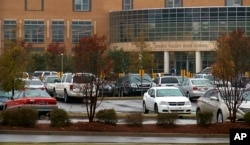 Cars sit in the parking lot, Oct. 27, 2015, in Columbia S.C. The Justice Department opened a civil rights investigation Tuesday after Senior Deputy Ben Fields flipped a student backward in her desk and tossed her across the floor for refusing to leave her