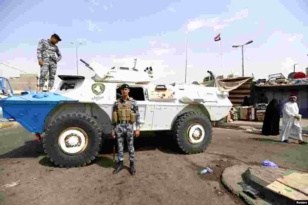Iraqi security forces stand guard at the site of a car bomb attack in the New Baghdad neighborhood, Aug. 26, 2014.
