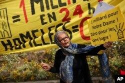 """Bir qadın aprelin 22-də Parisdə Notr Dam kilsəsinin önündə keçirilən etiraz zamanı əlində üzərində """"Notr Dam üçün bir saatda bir milyard! Evsizlər üçün sıfır"""" yazan plakat tutub."""