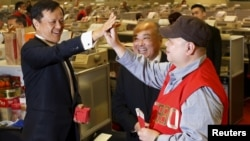FILE - Hong Kong Exchanges and Clearing Ltd Chief Executive Charles Li congratulates a floor trader after he received two 500 Hong Kong-dollar-notes as red packets on the first day of trading after Lunar New Year, Feb. 11, 2016.