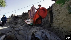 Rehmatud Din (c) who lost his daughter in Monday's earthquake, salvages what he can from his destroyed house caused by Monday's earthquake in Chitral town, northern Pakistan, October 29, 2015.