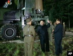 FILE - In this image made from video by North Korea's KRT on Friday, July 28, 2017, North Korean leader Kim Jung Un, center, gestures at the site of a missile test at an undisclosed location in North Korea.