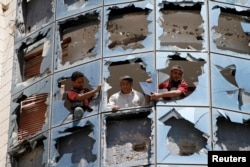 Workers clear broken glass from windows at a group of companies belonging to business tycoon Tawfeek Abdo Al-Raheem, which was damaged by fighting between Shi'ite Houthi rebels and government forces, in Sana'a, Sept. 28, 2014.
