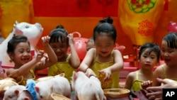 Anak-anak perempuan bermain-main dengan babi berukuran mini, sebuah hewan peliharaan langka di negara itu, di awal perayaan Tahun Baru Imlek, 1 Februari 2019 di Lucky Chinatown Plaza, Manila, Filipina (foto: AP Photo/Bullit Marquez)