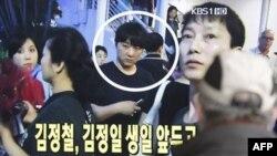 Một thanh niên Nam Triều Tiên đang xem tin trên TV, tại một trạm xe lửa, nói về Kim Jong Chol dự buổi trình diễn của Eric Clapton ở Singapore