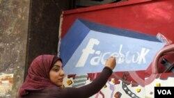 Seorang mahasiswi Universitas Helwan menggambar 'mural' Facebook di salah satu tembok di Kairo sebagai peringatan revolusi melengserkan Hosni Mubarak yang diorganisir melalu Facebook dan Twitter.