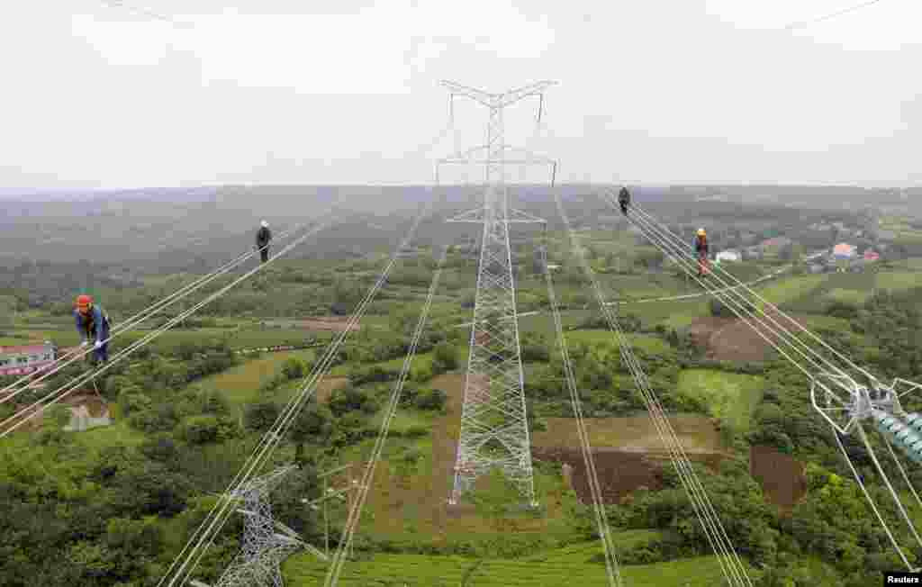Workers walk along wires as they inspect newly-built electricity pylons above crop fields in Chuzhou, Anhui province, China.