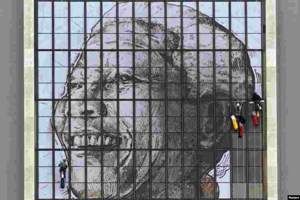 Rope access technicians work to complete a huge portrait of former South African President Nelson Mandela on the windows of the Civic Center building in Cape Town. Mandela is recovering well from a lung infection which has kept him in a serious condition in a hospital for a week.