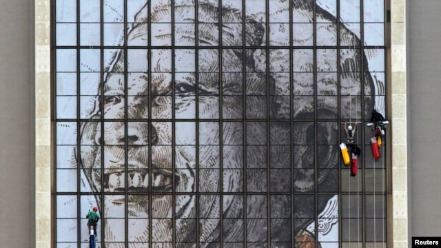 Rope access technicians work to complete a huge portrait of former South African President Nelson Mandela on the windows of the Civic Center building in Cape Town, June 15, 2013.