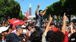 Protesters are seen gathered on the main avenue of Tunisia capital, Tunis, condemning the assassination of opposition leader Mohamed Brahmi, July 25, 2013.